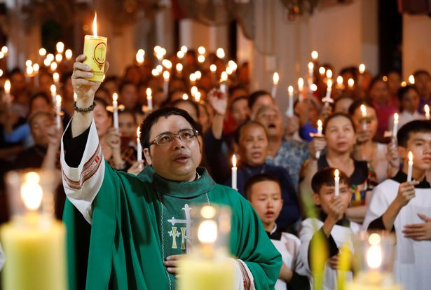 0_Catholic-priest-Anthony-Dang-Huu-Nam-holds-a-candle-during-a-mass-prayer-for-39-people-found-dead-in