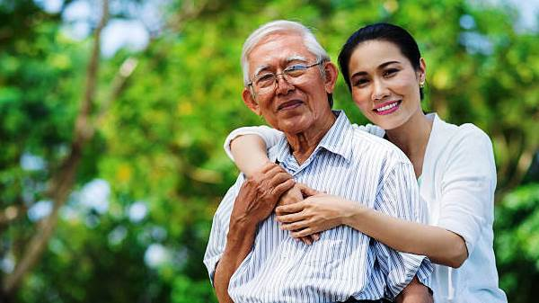 Portrait of smiling Vietnamese woman hugging her father
